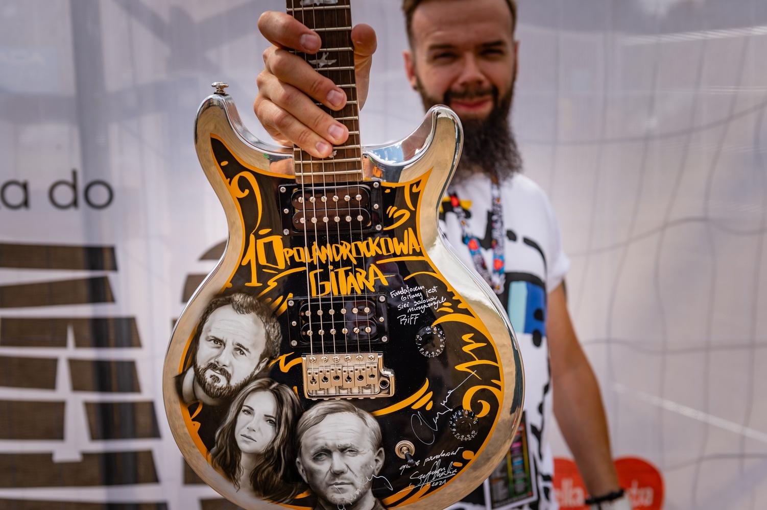 Front of the guitar with the images of Arkadiusz Jakubik, Kasia Kowalska and Andrzej Chyra (with an autograph) held by Szymon Chwalisz. photo by Paweł Krupka.